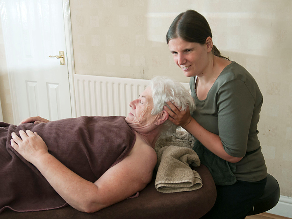 Dr Sarah Bryan of SB Holistic performing a head massage on a client